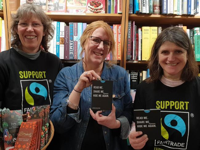 Ilkley Oxfam Bookshop manager and Ilkley Fairtrade Group members showcasing cocoa farmer 'storybombs' for the Fairtrade Fortnight quiz last year