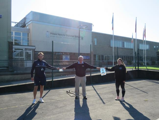 Otley Lions Dave Curtis and David McDowell with Fayme Yeates from Otley Netball Club at Prince Henry's Grammar School