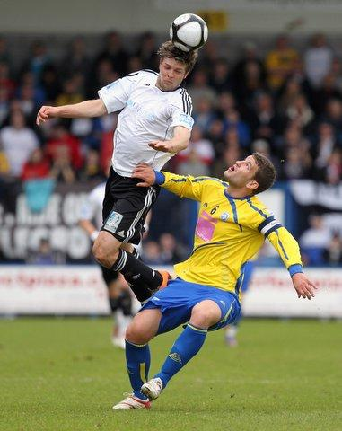 Andy Brown of AFC Telford United climbs above Simon Ainge of Guiseley