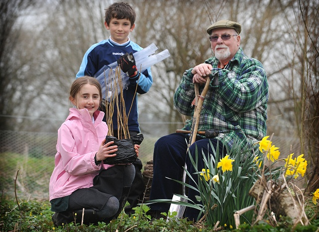 On the banks of the river in Poole-in-Wharfedale, children from Poole Church of England Primary help to plant the Jubilee Copse. Pictured are pupils Rebecca Bryant and Lewis Platt with Harry Wardman
