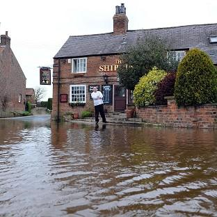 Richard Taylor looks at floodwater from the River Ouse as it rises to the steps of the Ship Inn at Acaster Malbis, near York