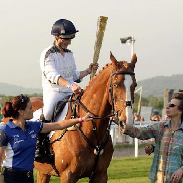 Zara Phillips, seen here carrying the Olympic Flame at Cheltenham Racecourse, has been selected to compete at London 2012