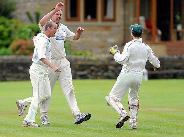 Otley's Ricky Halloran, centre, celebrates after another dismissal in his side's win over Steeton, who blew their chance of going top of Division One