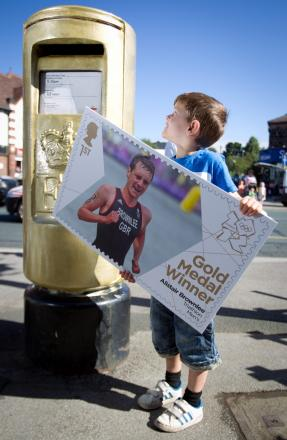 Six-year-old Joel Thirkell, right, tries to post a giant stamp marking Alistair Brownlee's gold medal triumph in the gold postbox in Horsforth in 2012. Pictures: Adam Gerrard
