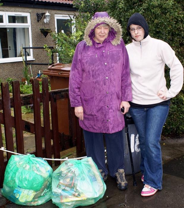 Wharfedale Observer: Jacky Francis, who is disabled, with the green bins she has had to put out for six months while waiting for a replacement from Leeds City Council, accompanied by her granddaughter, Sarah