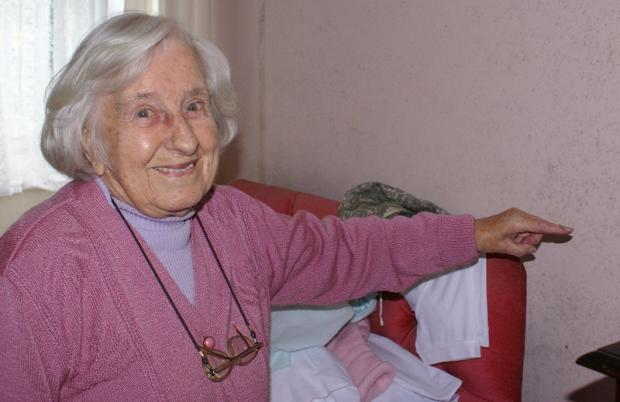 Pensioner Lillian Todd points to the damp wall in her sheltered flat in Otley