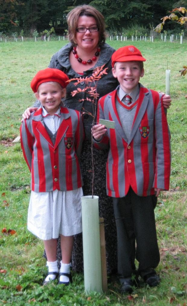 Ghyll Royd pupils Daisy Laxton, eight, left, and Harry Burns, nine, with headteacher, Jo Jenkinson, and one of the 200 new trees planted at their school