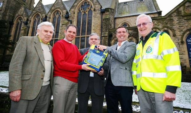 The Rev Rob Hilton, second left, receives the defibrilator from Richard Bradley, second right, watched by, from left, Geffrey De Vere, church steward Paul Ribbands and Alan Davies