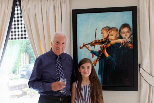 Artist Marshall Rubin with Ilkley musician Alexandra Keeley, in front of a portrait of Alexandra playing, painted by the artist