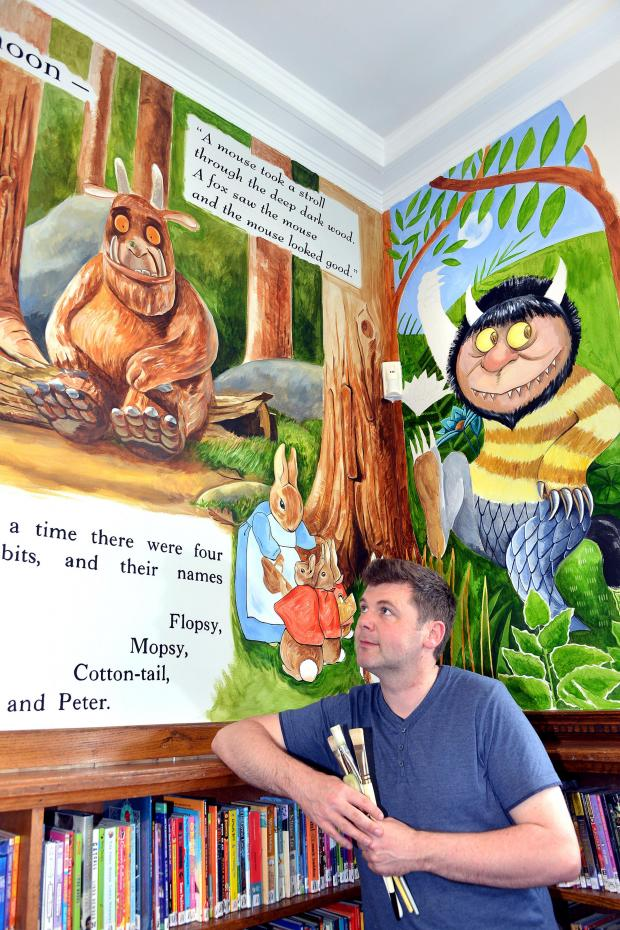 Wharfedale Observer: Ilkley  librarian John Giles has painted a mural in the children's section on one of the walls.