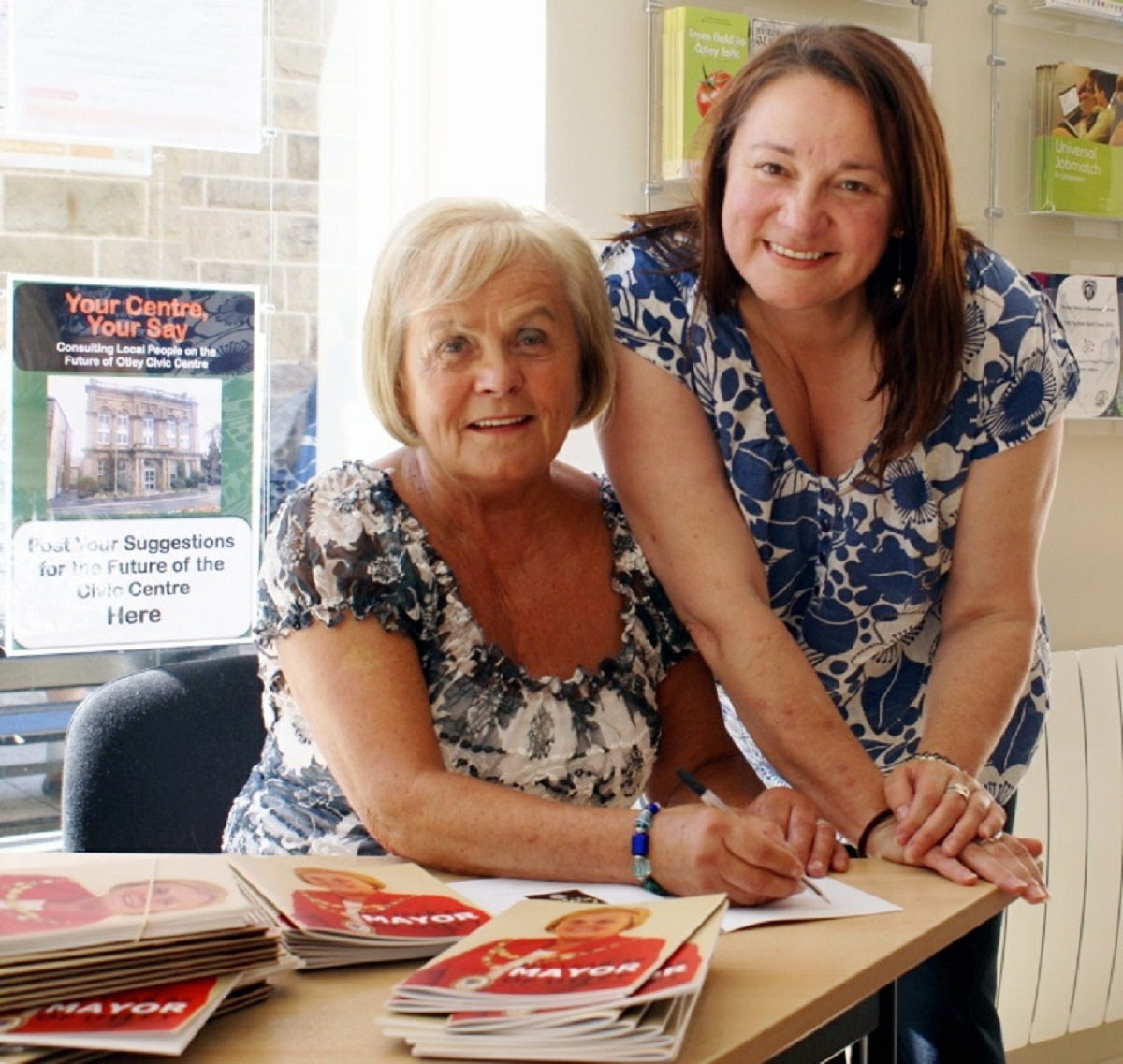 Councillor Mary Vickers (sitting) signing a copy of her new book, My Year as Mayor of Otley, with Otley Town Council executive officer Suzanne Kidger