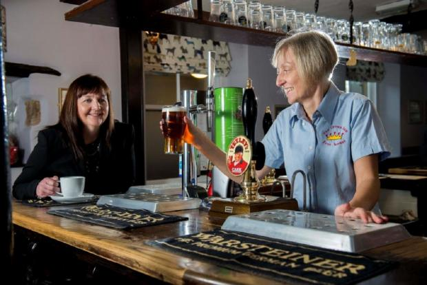 Landlady Maria Wells pulls a pint in her pub The Crown Inn, Addingham, for Elizabeth Smith of Natwest