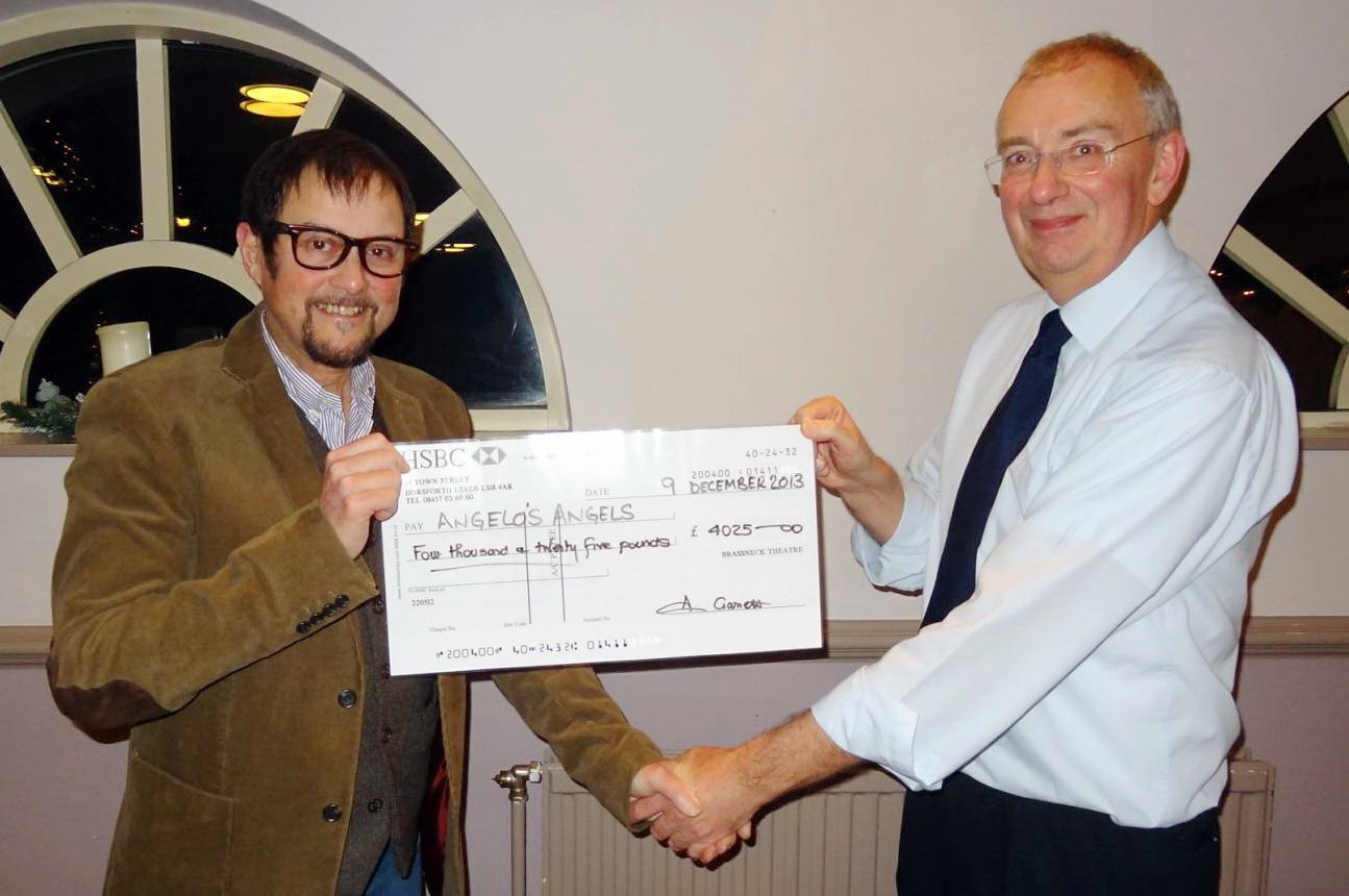 Angelo Clarke, left, receiving the annual charity donation from BrassNeck Theatre's Peter Cohen