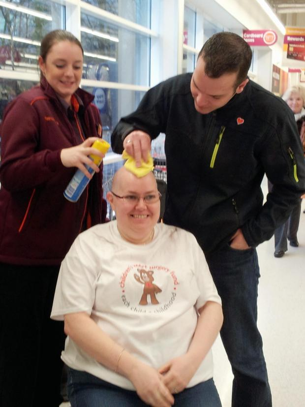 Wharfedale Observer: Hannah Reynard and Jamie Newson-Smith giving the final touches to Otley supermarket worker Kate Hobson's sponsored head-shave for a cause very close to the couple's heart