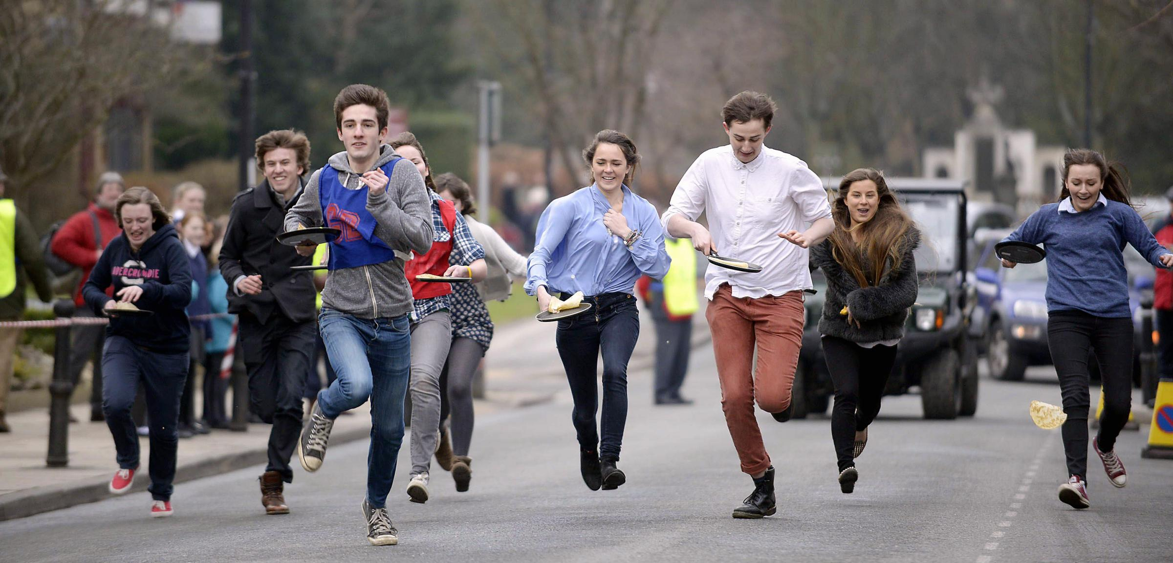 Students taking part in the Ilkley Pancake Race on The Grove last year