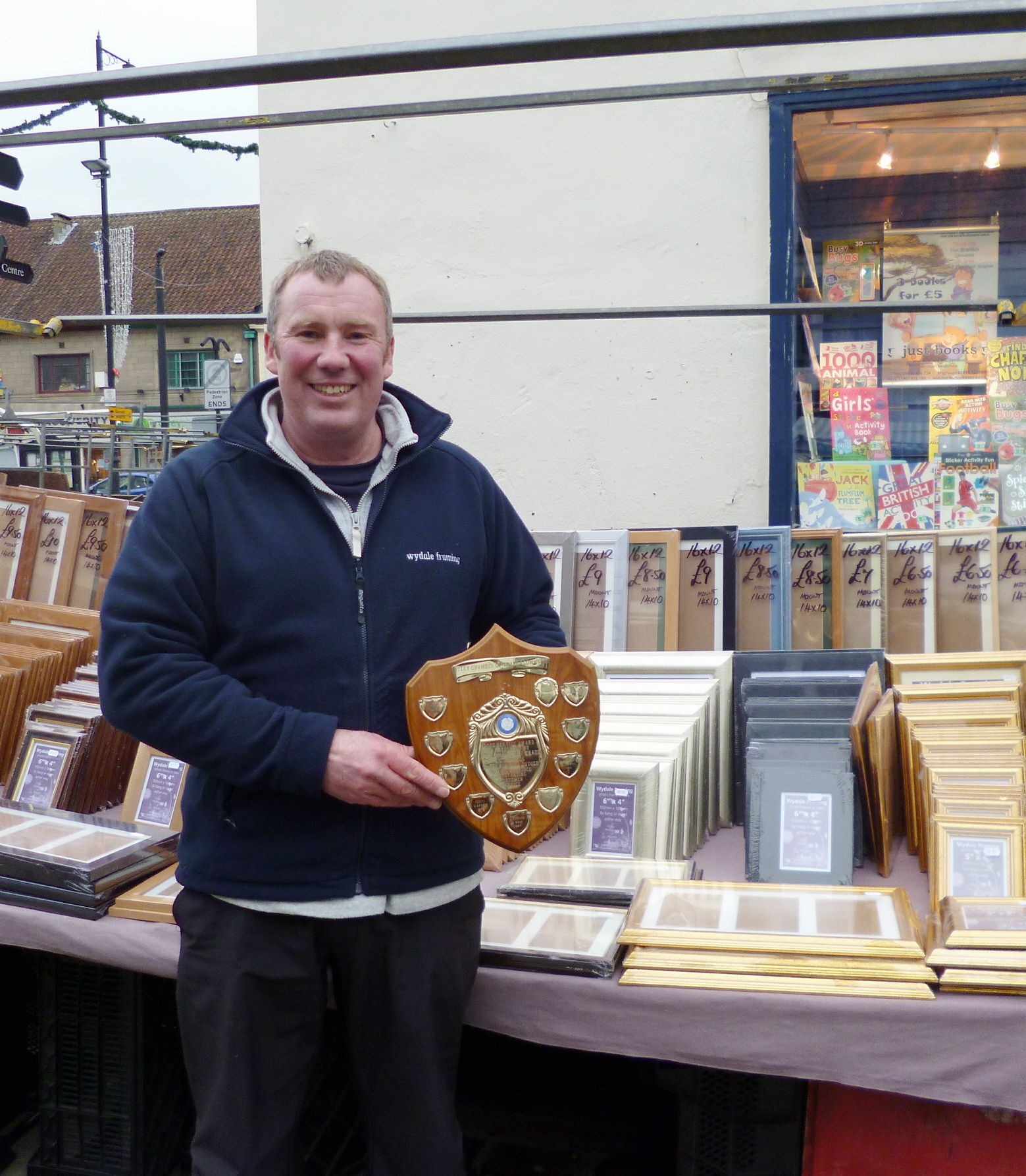 Andrew Halliday from Wydale Framing at Otley Market with the 2013 Otley Chamber of Trade Good Service Award shield