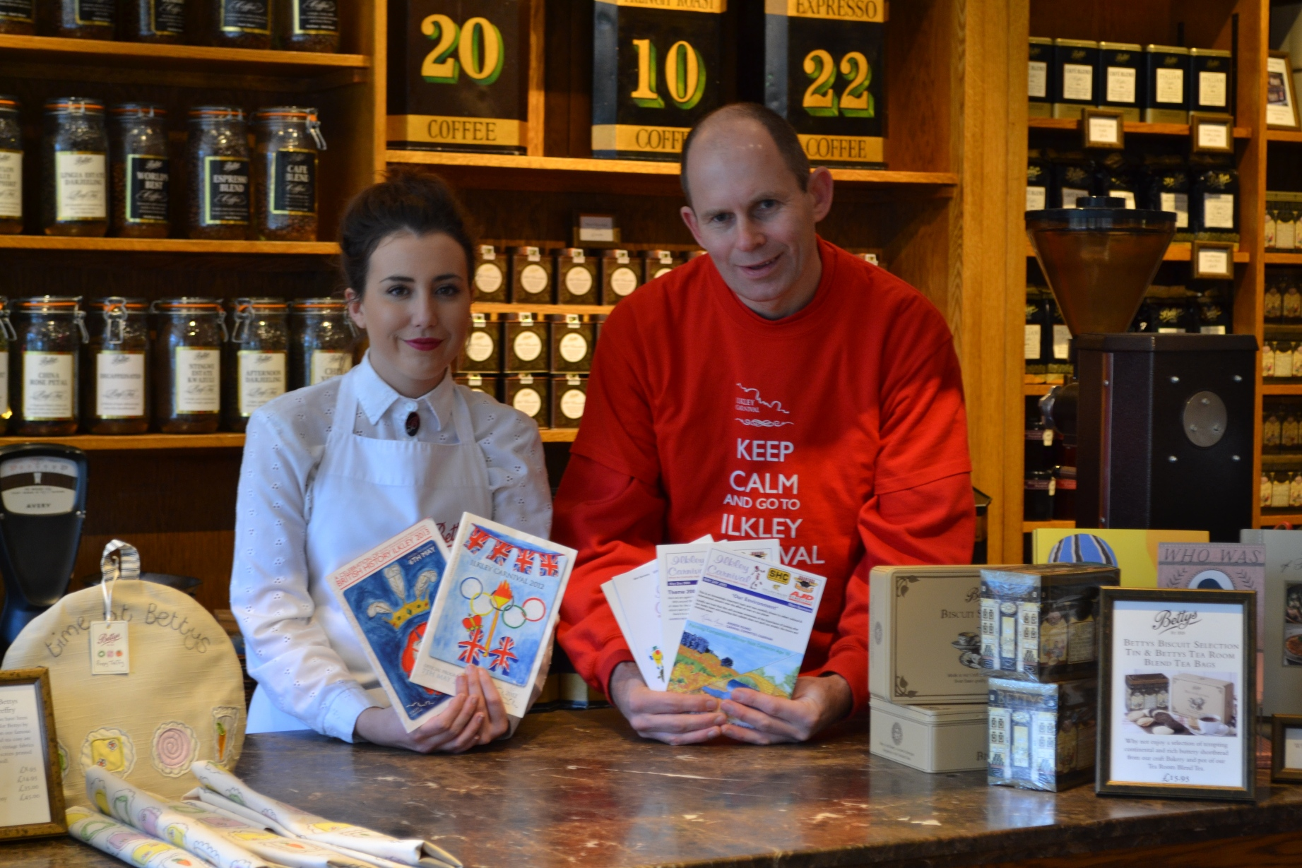 Bettys retail assistant Chloe Burns and Ilkley Carnival chairman Andrew Stacey, launch the 2014 Ilkley Carnival Cover Competition in Bettys in Ilkley with a look back at the event's programmes from the past decade