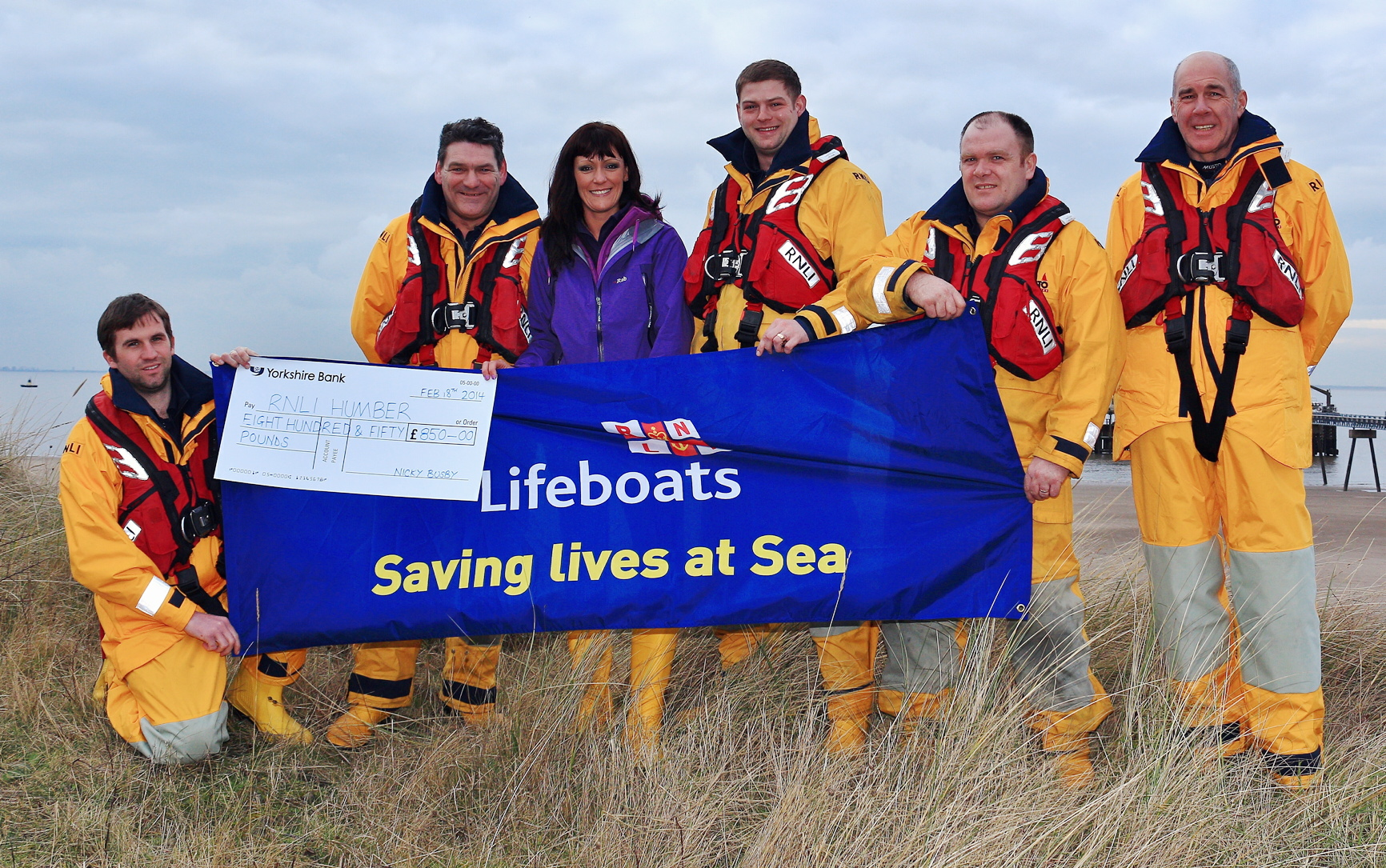 Fundraiser Nicky Busby presenting the cheque to the RNLI Humber crew. Picture by John Earnshaw