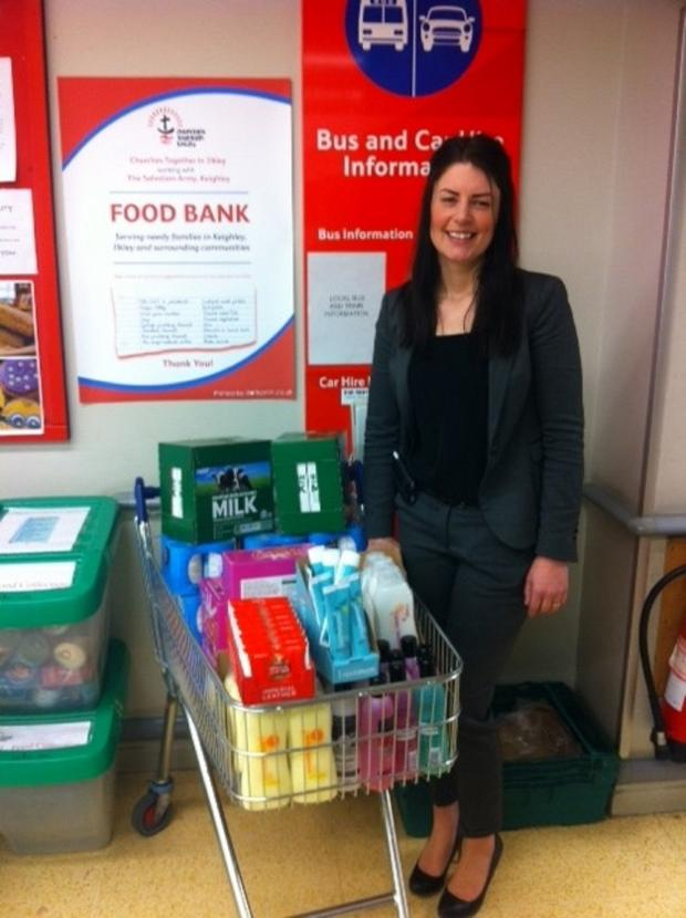 Wharfedale Observer: Ilkley Tesco manager Marie Torra with the trolley loaded with goods for the food bank, bought with the money raised from the project