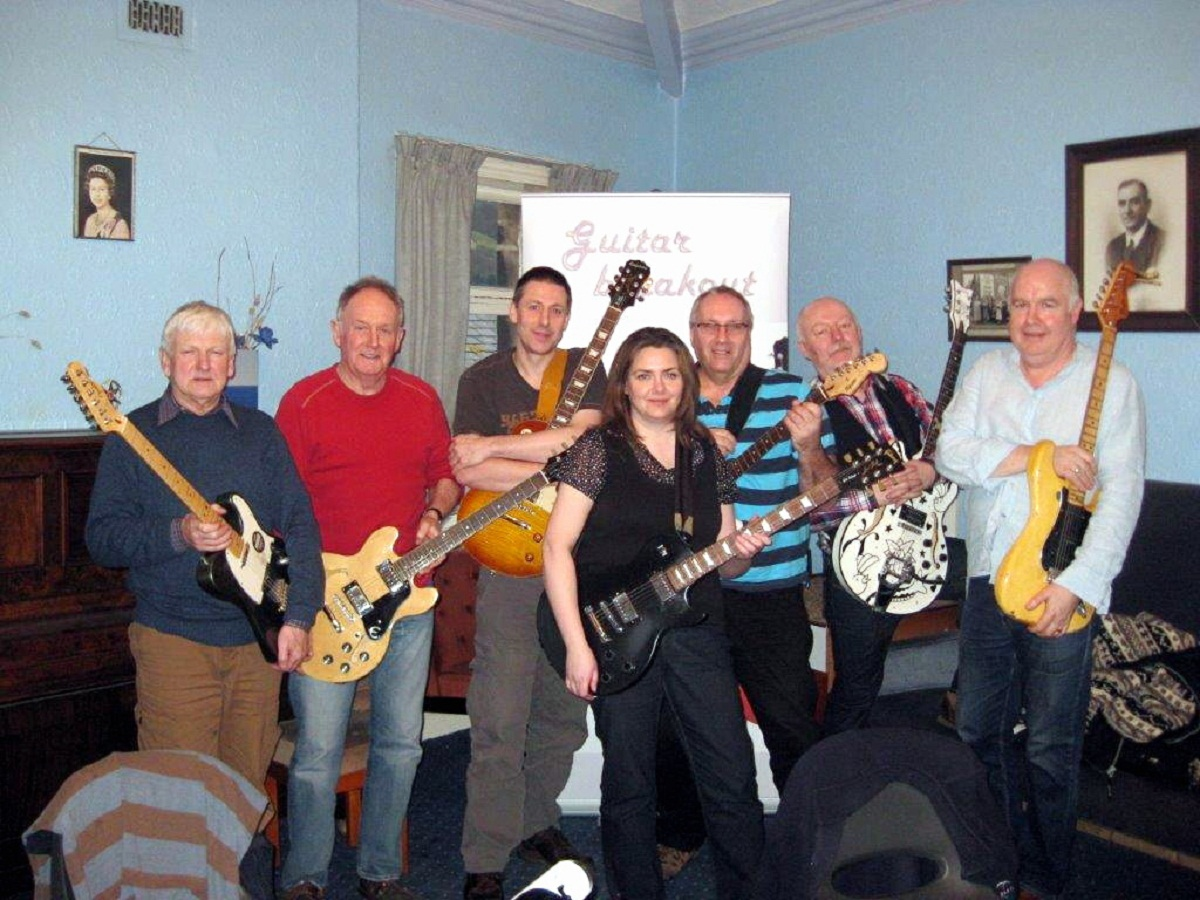 Guitar Breakout tutors Mike Massen, second from right, and Joe Gallagher, right, with reporter Amanda Greaves, front, and other members of the Beginners' Blues course