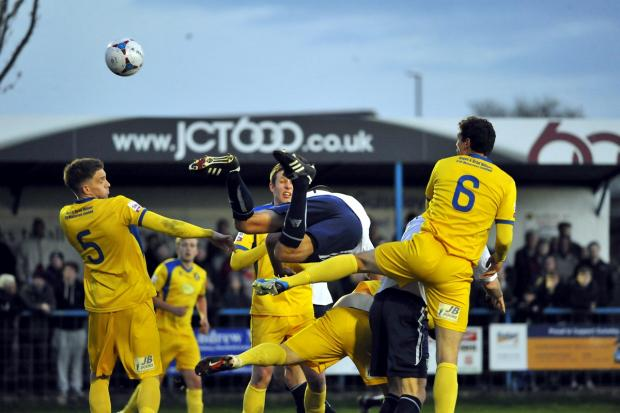 Wharfedale Observer: Guiseley's Danny Hall goes flying as he tanngles with the Gainsborough Trinity defence