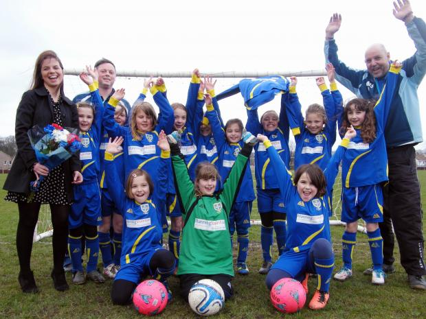 The Guiseley Under 9s Girls football team and their manager proudly showing off their new kits with Clare Frieze, manager of the Guiseley branch of Manning Stainton