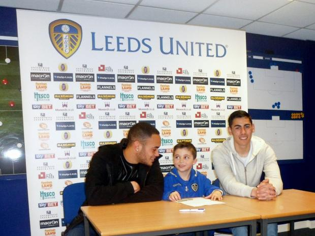 Wharfedale Observer: Sami Pattinson signing for the Leeds United Academy under-nine squad with United players Lewis Walters (left) and Eric Grimes