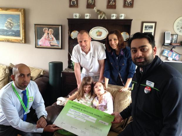 Baildon Co-op manager Khalid Mahmood, Mark and Radka Wormald and Menston store manager Kamran Khan, with seven-year-old Emily and Charlotte Wormald