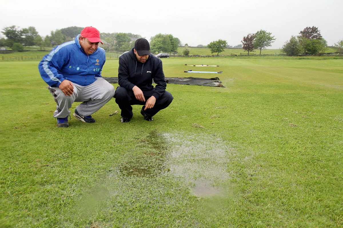 Wasim Hussain, left, and Nadeem Safdar inspect the waterlogged wicket at Ingrow St John's' ground, where the Mewies Solicitors Craven League match was called off before it started