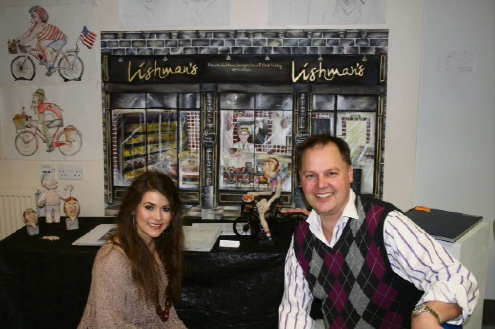 IGS A level art student  Alice Vaughan with David Lishman in front of Alice's art work depicting David's shop in Ilkley.