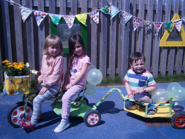 OLYMPUS DIGITAL CAMERA (7175970)Iris Smith (3), Halle Kirkbride (4) and Harry Naylor (4) of Ben Rhydding Pre-School get on their bike ready for Ben Rhydding Community Fete
