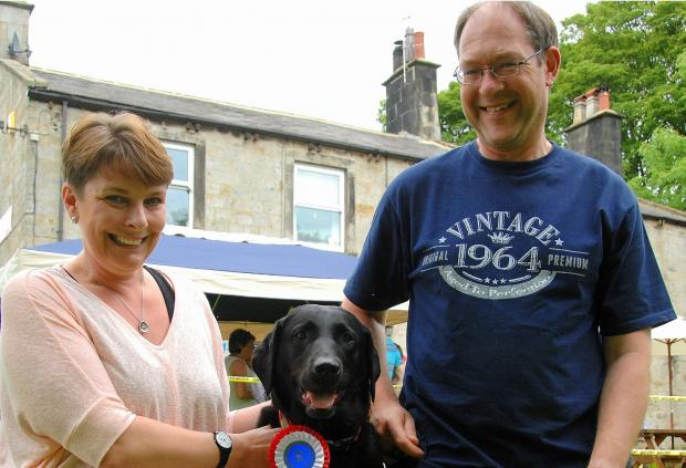 Wharfedale Observer: Cock Pit Farm Tea Rooms' owner Sue Sansbury with 'best in show' winner Max, a veteran rescue Labrador, and his owner Paul.