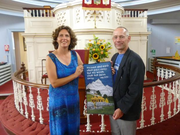 Sarah and Paul Wright with the tapestry they have presented as a token of thanks to Otley Methodist Church following their long overseas mission.