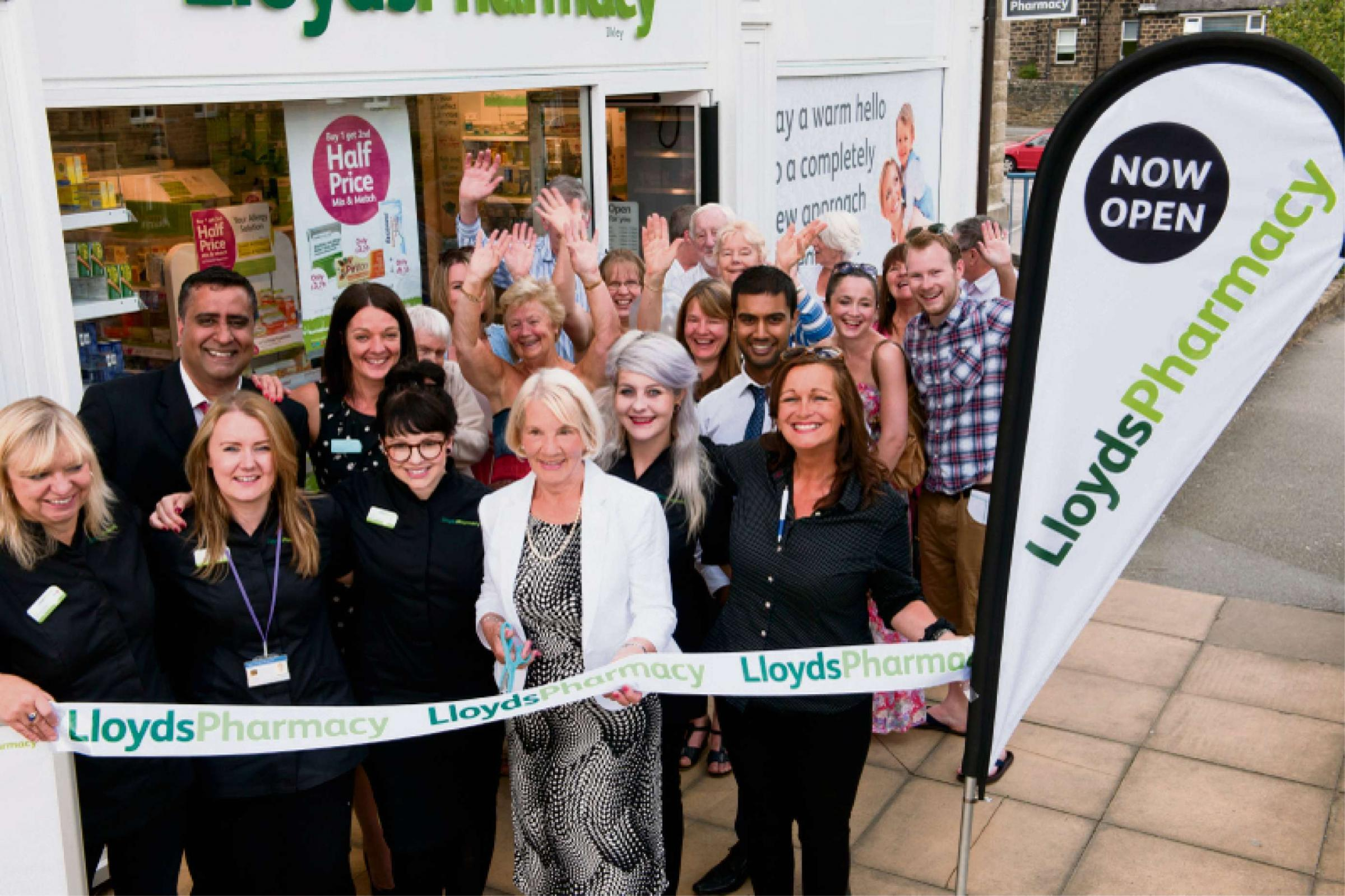 At the cutting edge of health: Mary Hume (centre) cuts the ribbon with pharmacy manager Chico Vyas (second from left) and his team applauding.