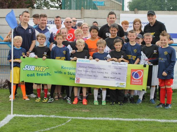 Pictured – left to right with the children are:   Brian Curran of Heart Research UK, Vicki Hepworth, Trustee of Guiseley Community Foundation; Mark Bower, 1st Team Manager GAFC;  Lara Dawes and Ian Dawes from SUBWAY®  stores.