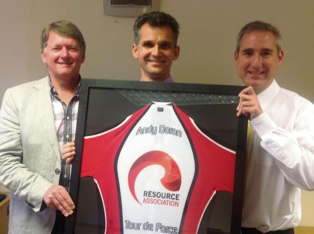 Retiring chairman of the Resource Association, Andy Doran (centre), receiving his framed, personalised cycling shirt  from new chairman Jonathan Short (left) and MP Greg Mulholland (right).