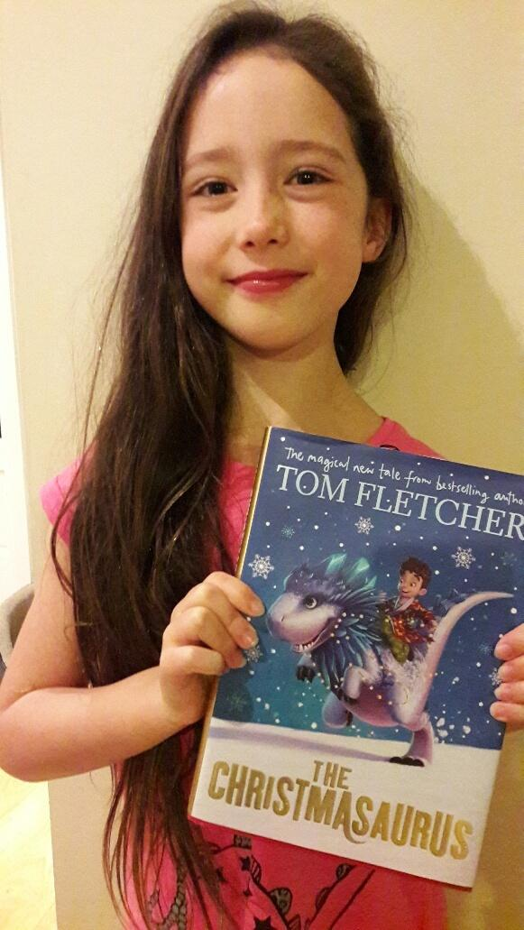 Eight-year old Eve Allen with her copy of Tom Fletcher's The Christmasaurus, which she loved so much she read it in two days
