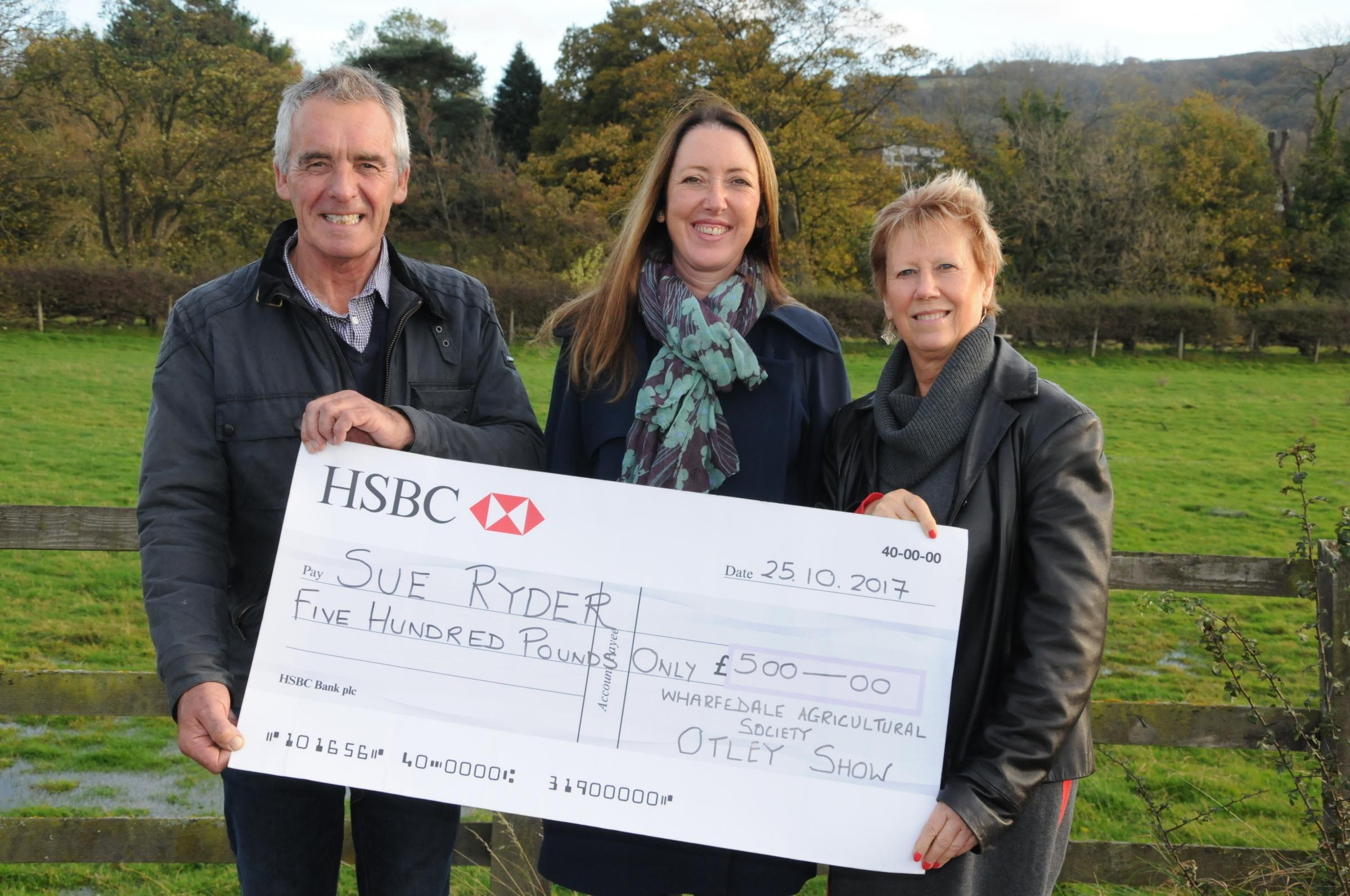 Richard Houldsworth of Basil Houldsworth and Sons and Otley Show Secretary Janet Raw presenting Kirsty Christmas (centre) with a £500 cheque for Sue Ryder Wheatfields Hospice. Photograph by Andrew Beeson.