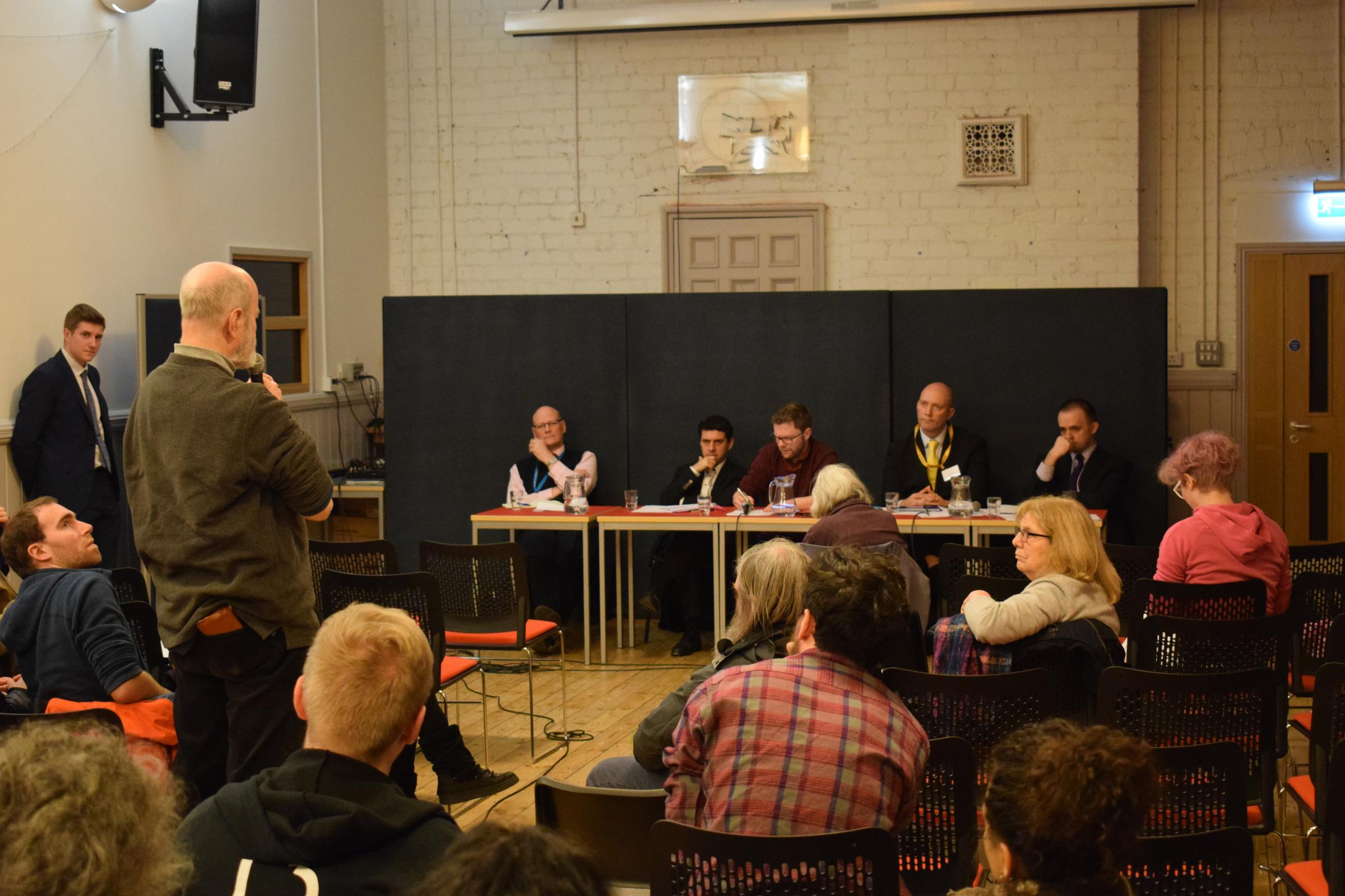 A passenger raising an issue with representatives from First Bus at a public meeting organised by MP Alex Sobel (seated at desk, second left)