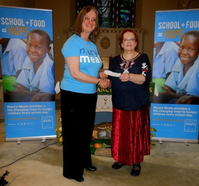 Otley Town Councillor Penny Robinson (right) presenting a cheque to a representative from Mary's Meals